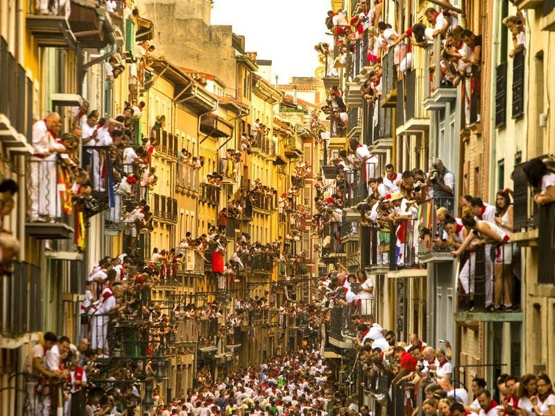 People watch as revelers run in front of Jandilla bulls at the San Fermin festival, in Pamplona, Spain. (AP Photo/Andres Kudacki)