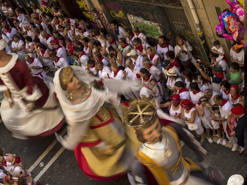 The Giant Parade passing down a street, at the San Fermin Festival. (AP Photo/Alvaro Barrientos)