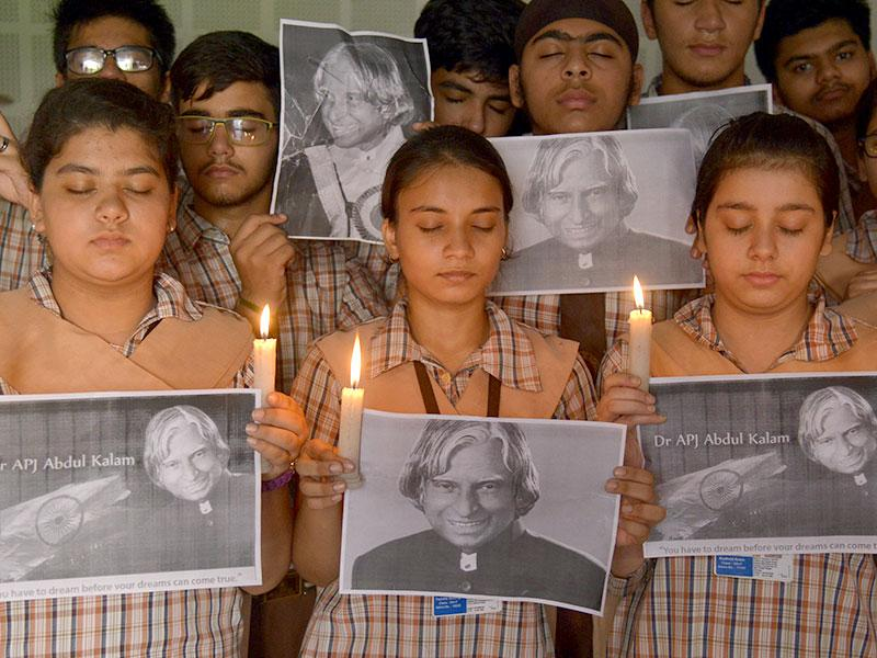 School children hold candles as they pay homage to India's former president APJ Abdul Kalam at a school in Amritsar. (AFP Photo)