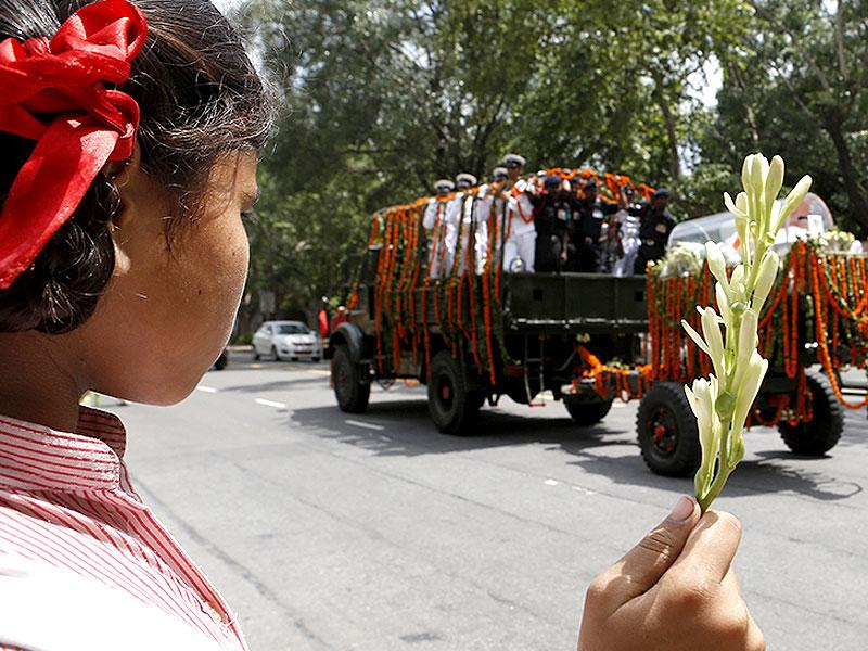 A girl holds flowers as children wait to pay tribute to former Indian president APJ Abdul Kalam while his body is transported from the airport to his house in New Delhi. (HT Photo/Ravi Choudhary)