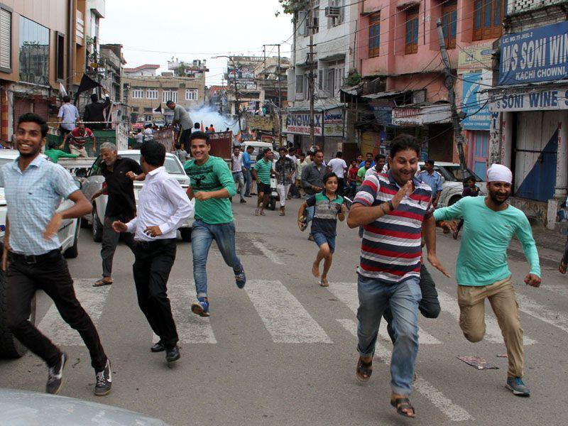 People running after a tear gas shell is fired by police in Jammu.(HT File)