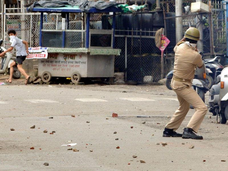 A boy runs to take shelter as the policeman throws a smoke shell in his direction (Nitin Kanotra/HT)