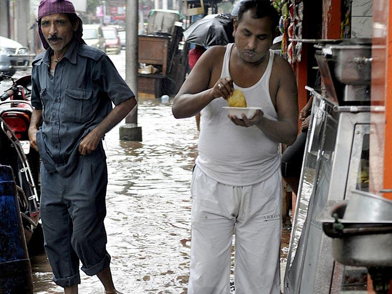 A man having snacks while standing on a flooded road in central Kolkata. (Ashok Nath Dey/ HT Photo)