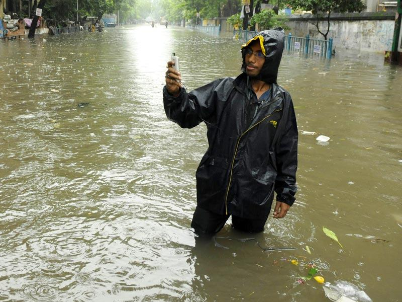 A boy takes a selfie on a flooded street at Amherst Street in central Kolkata. (Samir Jana/HT Photo)