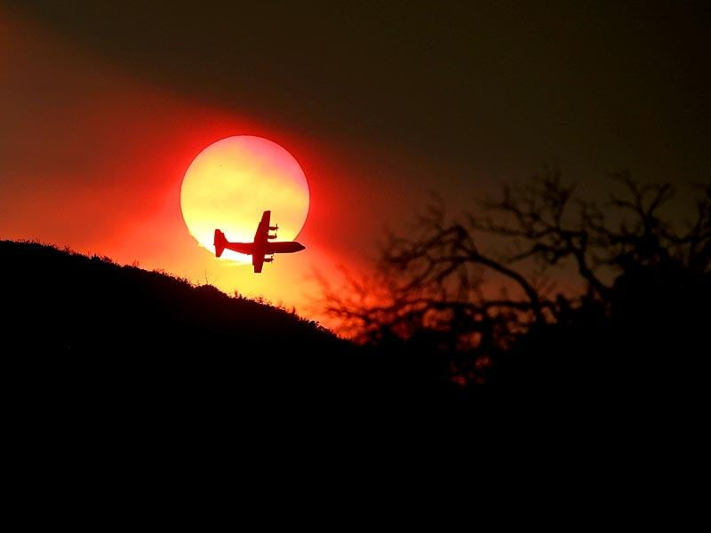 A firefighting air tanker flies in front of the setting sun while battling the Rocky Fire near Clearlake, California. (AFP Photo)