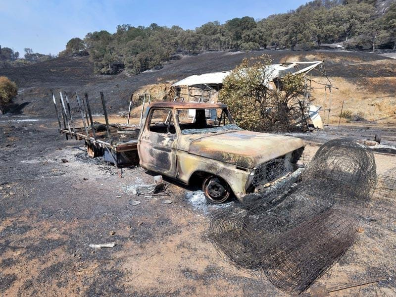 A burned out truck sits on an evacuated property as fire personnel battle the Rocky fire near South Lake, California. (AFP Photo)