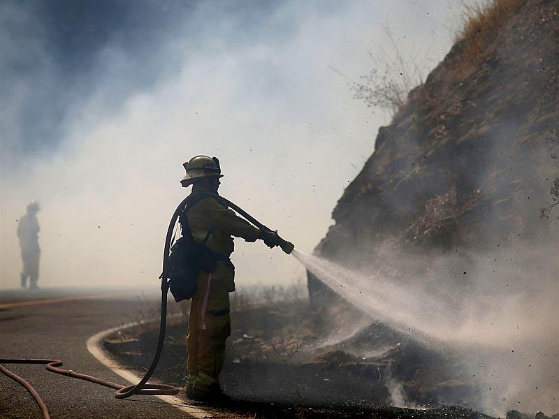 A Long Beach firefighter mops up hot spots after the Rocky Fire burned a hillside in Lower Lake, California. (AFP Photo)