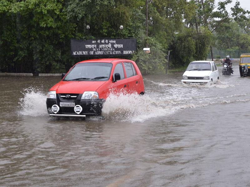 Vehicles wade through a waterlogged road in front of Academy of Administration as heavy showers lashed Bhopal on Sunday. (Mujeeb Faruqui/HT photo)
