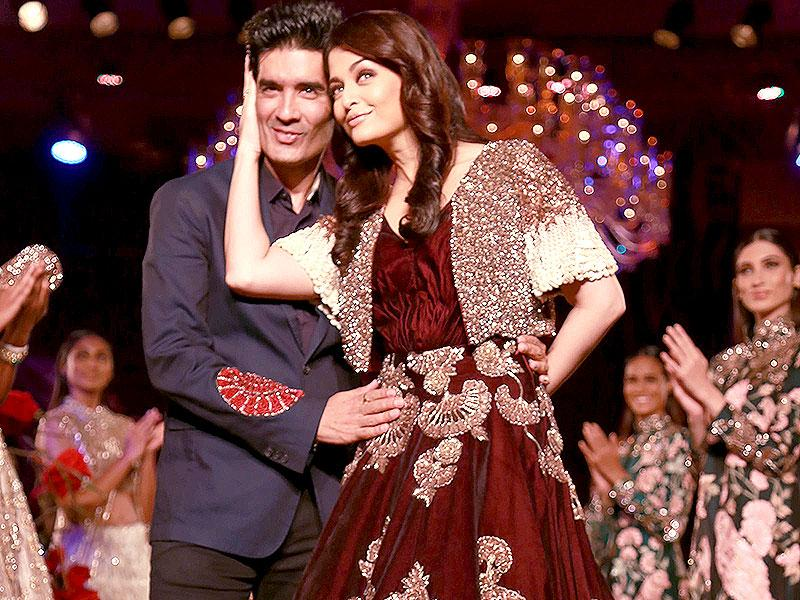 Aishwarya and Manish Malhotra strike a pose as the former Miss World walked the ramp in one of the designer's creation. (AP photo)