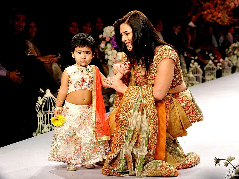 Actor Urvashi Sharma with her young daughter Samaira Joshi showcases a creation during India International Jewellery Week 2015 in Mumbai. (AFP photo)