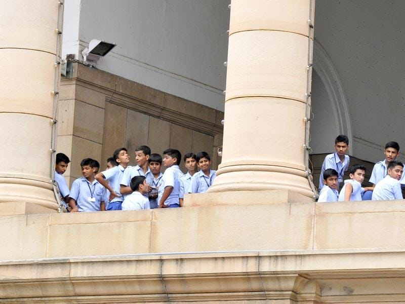 School students look at the Congress members as they protest aginst NDA govenment near Gandhi Statue at Parliament complex. (Sonu Mehta/HT Photo)