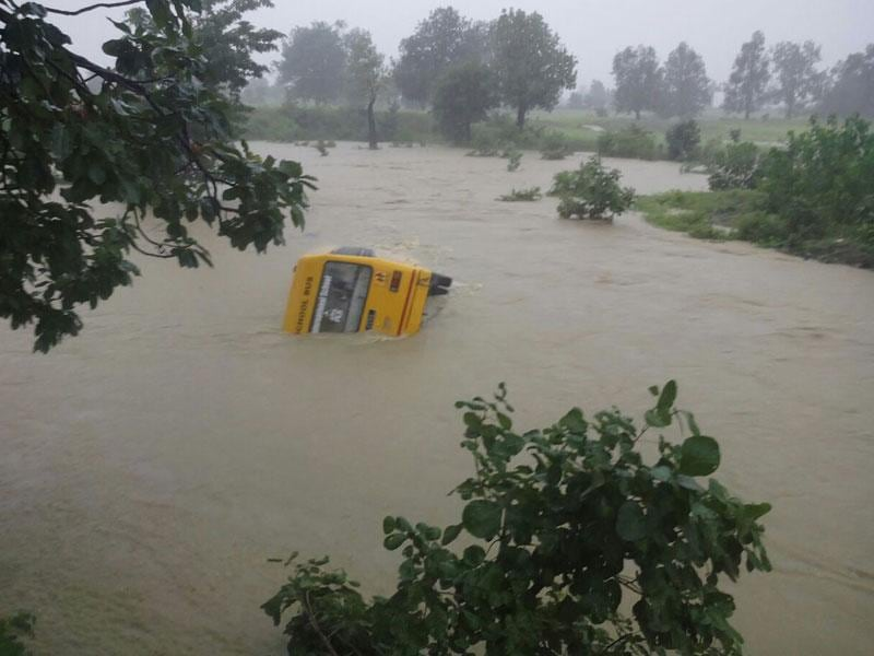 A school bus in Chor Pandra village of Betul was swept away on Tuesday as a river stream was in spate. All the children were rescued. (HT)