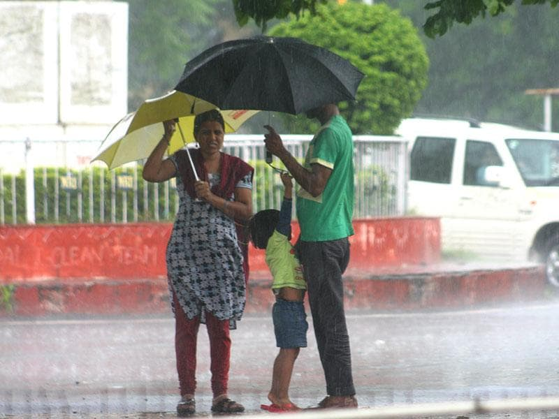 Residents protect them from showers in Bhopal on Tuesday.(Bidesh Manna/HT photo)