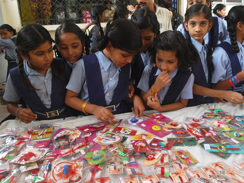 Students of the Gujarati School look at the rakhis made by their fellow classmates during an exhibition organised on school campus in Indore. (Shankar Mourya/HT)