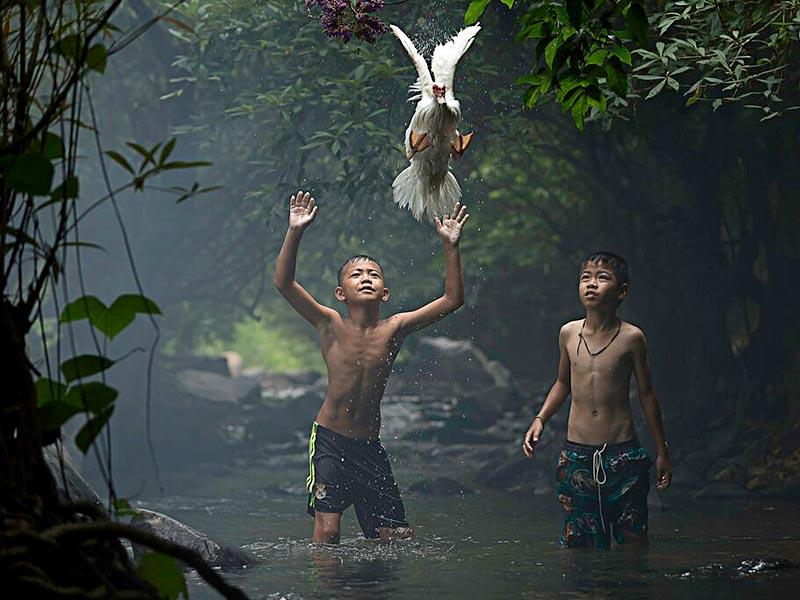 Catching a Duck | Two boys are trying to catch a duck at the stream of the waterfall. Nong Khai Province, Thailand (Photo and caption by Sarah Wouters /National Geographic Traveler Photo Contest. Here are the details about the contest http://travel.nationalgeographic.com/photo-contest-2015/)