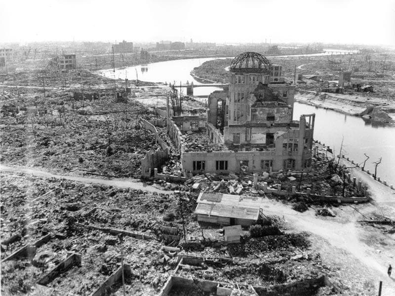 In this Sept 8, 1945 file photo, an allied correspondent stands in the rubble in front of the shell of a building that once was a exhibition center and government office in Hiroshima, Japan, a month after the first atomic bomb ever used in warfare was dropped by the US on Aug. 6, 1945. (AP Photo/Stanley Troutman, File)