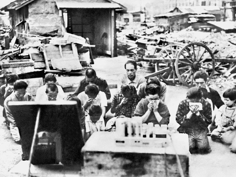 In this Aug 15, 1945 photo, people kneel and listen to the radio in Tokyo, as Emperor Hirohito announced on radio that Japan was defeated in the World War II. (Kyodo News via AP)