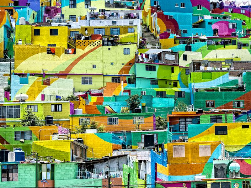 Residents had to be convinced to let artists paint their house walls before the project began. 'Las Palmitas' was first painted white after which artists created the mural. (AFP Photo)