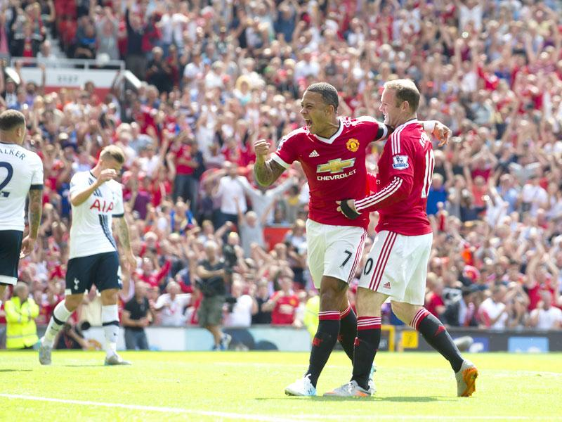 Manchester United's Wayne Rooney (R) celebrates with teammate Memphis Depay after an own goal by Tottenham's Kyle Walker (R) during the English Premier League (EPL) match between Manchester United and Tottenham at Old Trafford in Manchester on August 8, 2015. (AP Photo)