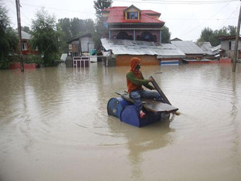 A man sailing on makeshift plank in flooded waters of Srinagar. HT File Photo