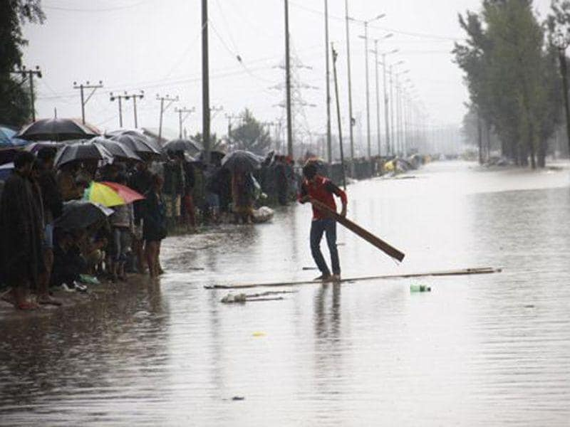 A man sailing on wooden plank in flooded waters in Srinagar. HT File Photo