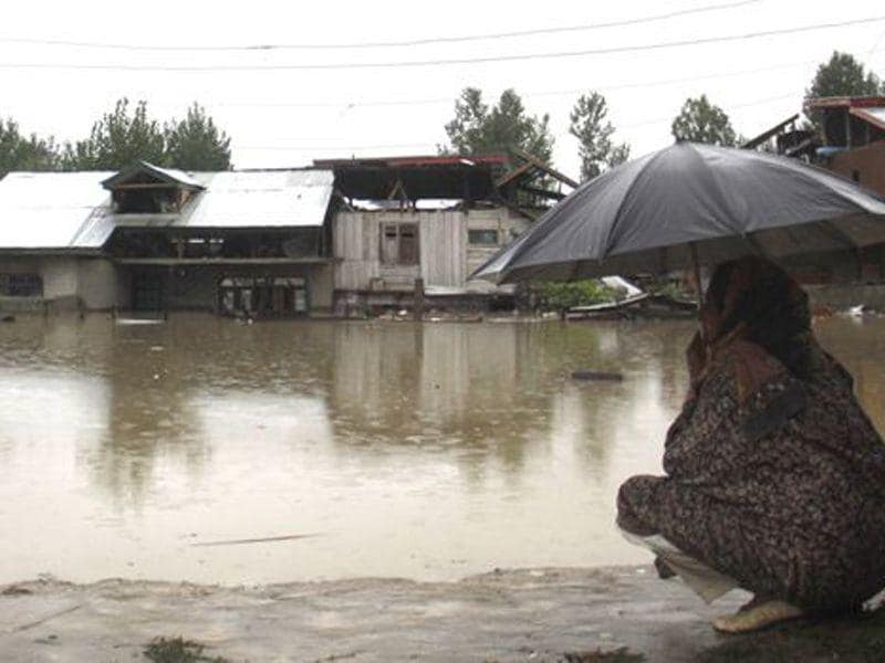 A woman looks at a flooded houses in Srinagar. HT File Photo