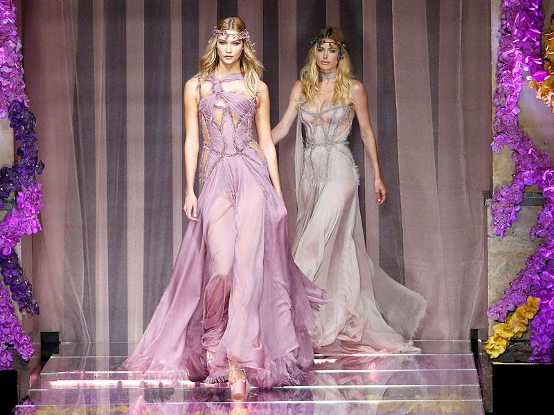 Versace creation boasted of subdued colours and lots of jewels. 'Flower fairies' walked the ramp in flowy dazzling gowns. US model Karlie Kloss presents a creation by designer Italian designer Donatella Versace. (Reuters/ Charles Platiau)
