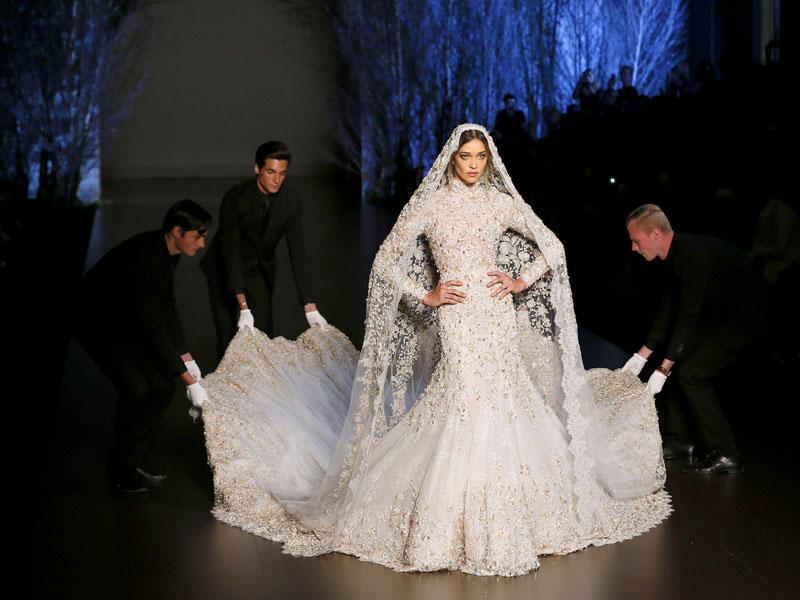 Inspired by romance were Ralph&Russo creations. Brazilian model Ana Beatriz Barros showcases a stunning off-white bejewelled bridal gown. (AFP Photo/ Patrick Kovarik)
