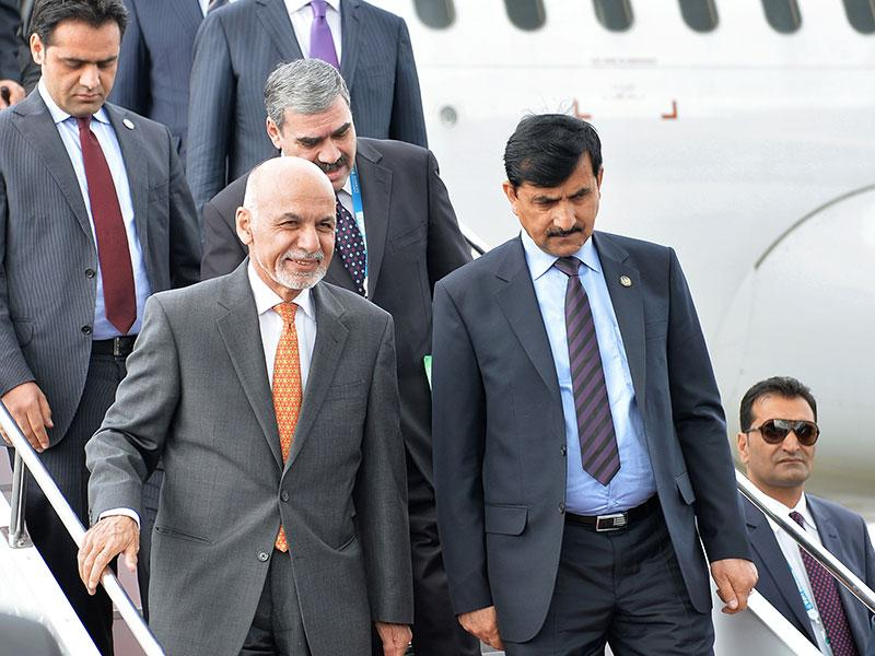 Afghanistan President Ashraf Ghani Ahmadzai (front left) and members of his delegation walk down the stairs upon arrival in Ufa. (Host photo agency/RIA Novosti Pool Photo via AP)