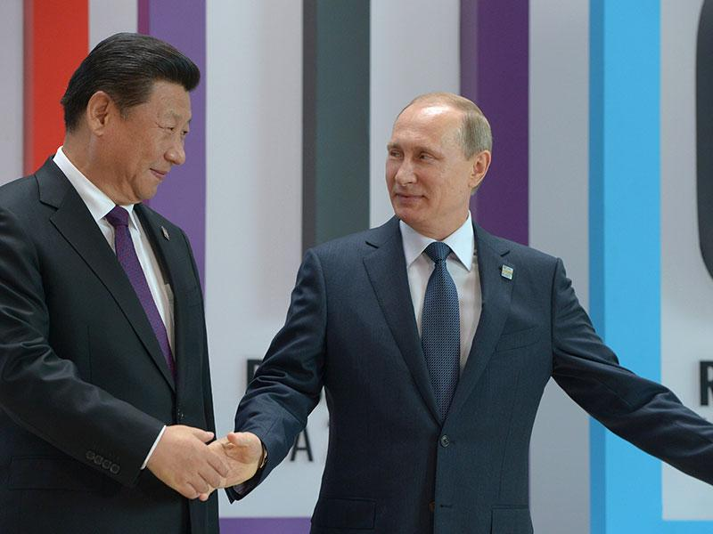 Russian President Putin, right, and China's Xi Jinping shake hands during welcome ceremony. (Host photo agency/RIA Novosti Pool Photo via AP)