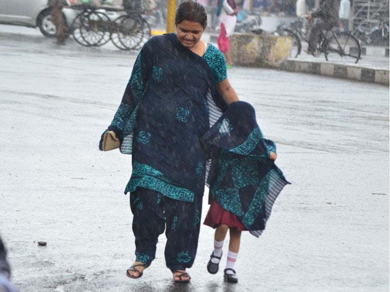 Light to moderate showers lashed Bhopal on Thursday after a long interval. A girl covers herself with her mother's dupatta to save her from rain. (HT photo)