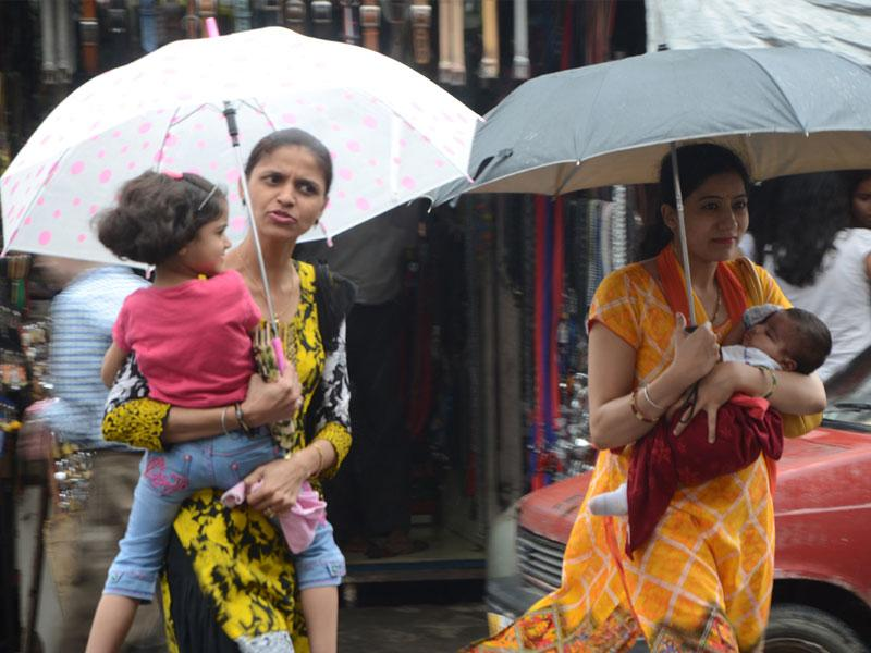 Residents protect them from showers in Bhopal on Saturday. (Bidesh Manna/HT photo)