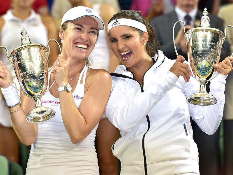 Martina Hingis (L) and Sania Mirza (R) pose with the winner's trophies. For Mirza, it was a maiden women's doubles title at a Grand Slam although she has won three mixed doubles at the majors. It came 12 years after she turned Pro. (AFP Photo)