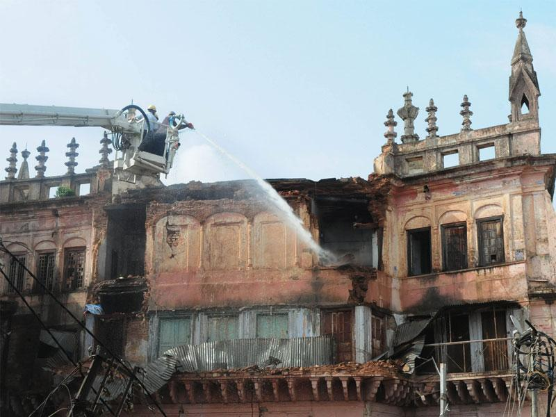 Bhopal Municipal Corporation workers using water to raze dilapidated parts of historical Shaukat Mahal, in Bhopal on Sunday. (Mujeeb Faruqui/HT)