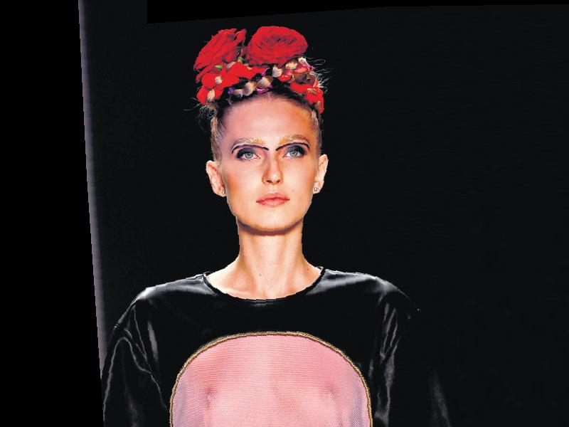Floral accents on milkmaid braids seen at a show by Rebekka Ruétz at the Berlin Fashion Week.