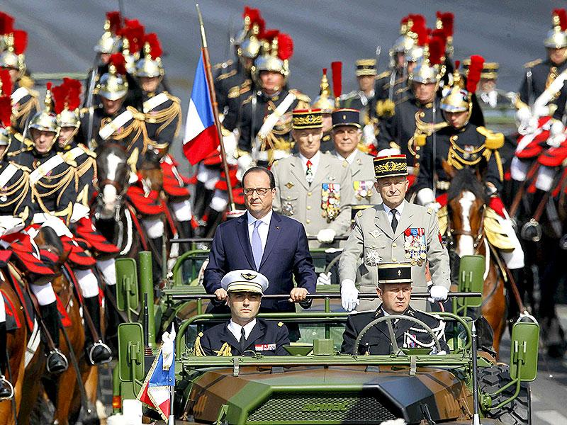 In a traditional beginning to the celebrations, French President Francois Hollande stands at attention in the command car as he reviews the troops while descending from the Champs Elysees. (Reuters/Mal Langsdon)
