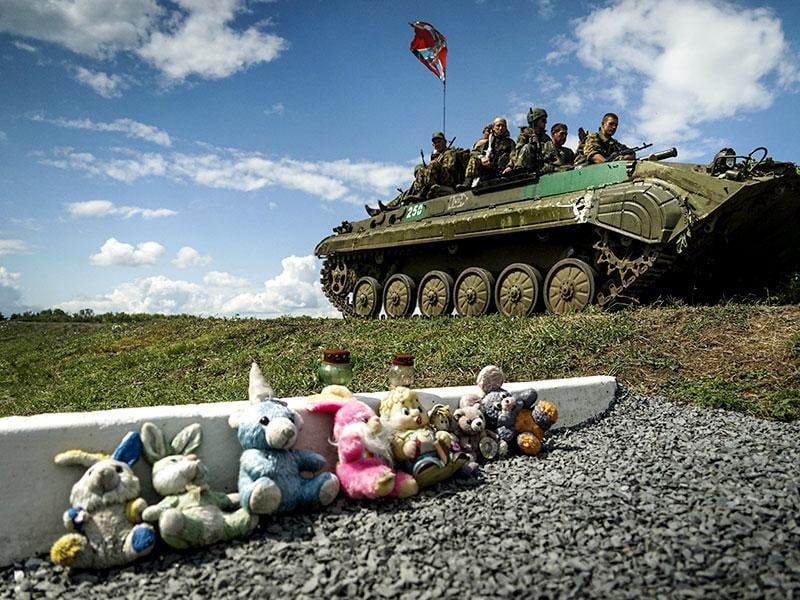 Russian-backed separatist APC with a flag of the self-proclaimed Federal State of Novorossiya, rides by a memorial for victims of the MH17 plane crash, near the village of Hrabove, eastern Ukraine. It has been a year since the Malaysia Airlines Boeing 777 was shot down in war-ravaged eastern Ukraine. (AP Photo)