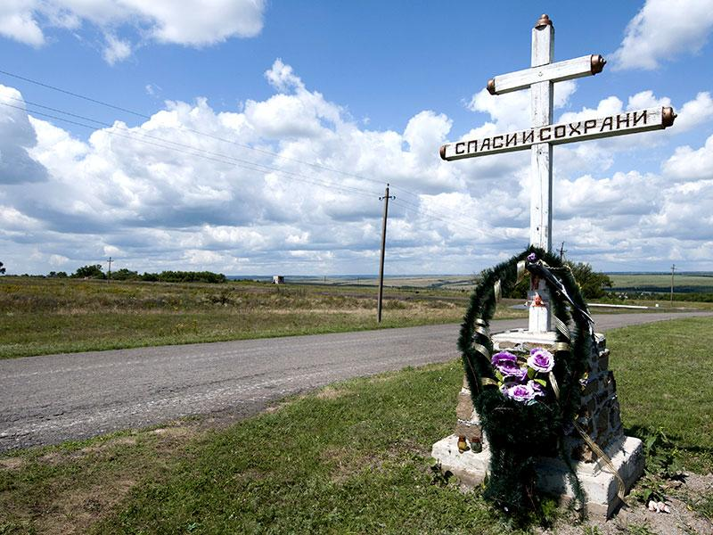 An orthodox cross with a sign reading Save and Guard is placed at the site of the crashed MH17 plane, near the village of Hrabove, eastern Ukraine. The fighters said they had arrived to protect the media and make sure the crash site is clear of ammunition and mines. (AP Photo)