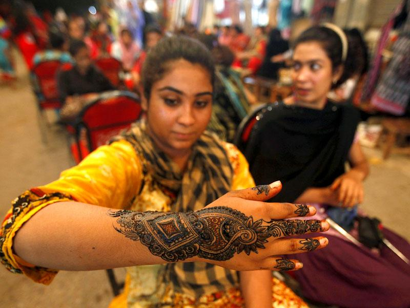 A girl shows her hand decorated with traditional henna patterns at a roadside stall ahead of Eid-ul Fitr to mark the end of the holy fasting month of Ramzan in Karachi, Pakistan (REUTERS Photo)