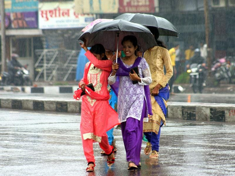 Girls protect themselves from the monsoon showers in Bhopal. (Bidesh Manna/HT photo)