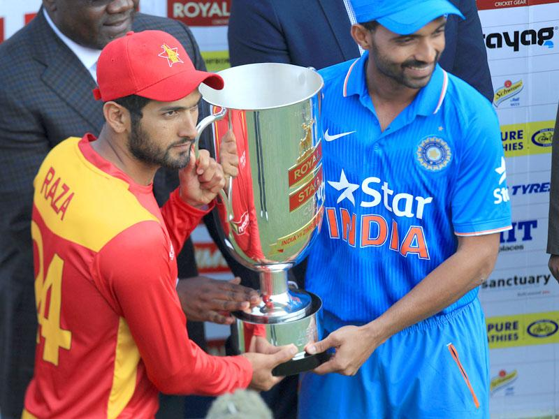 Stand-in Zimbabwe captain Sikandar Raza, left, and Indian captain Ajinkya Rahane share the trophy after the Twenty20 series ended 1-1 in Harare, Zimbabwe, on July 19, 2015. (AP Photo)
