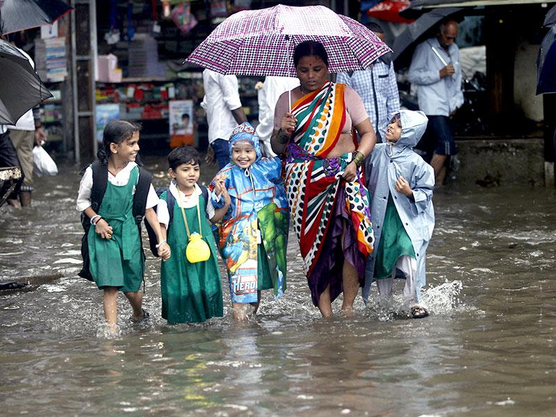 School children wade through water-logged road of Kurla after heavy rains lashed Mumbai and suburbs. (Arijit Sen/HT photo)