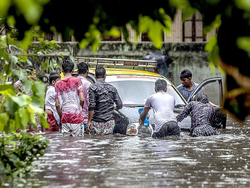 People push a taxi on a water-logged street at Sion after heavy rains lashed Mumbai and suburbs. (Kunal Patil/HT photo)