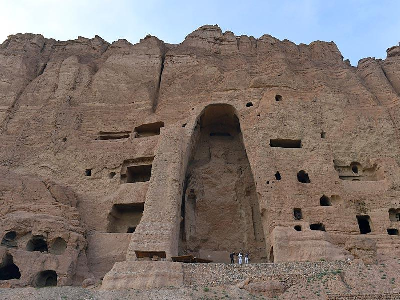 Visitors walk in front of the empty site of two Buddha statues, which were destroyed by the Taliban, in Bamiyan.(AFP Photo)