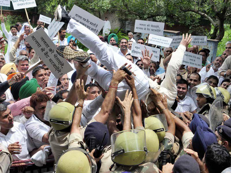 Several Indian National Lok Dal (INLD) members, including MP Dushyant Chautala, tried to cross over the barricades put up by the police during their protest against the recent hike in VAT on diesel, in Chandigarh on Wednesday. (Gurpreet Singh/HT)
