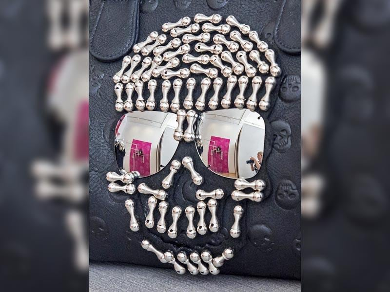 A woman with a camera is reflected in a handbag with skull motiffs during the press preview at the exhibition Sepuchral Store- Buy now, die later! (AP Photo/Jens Meyer)