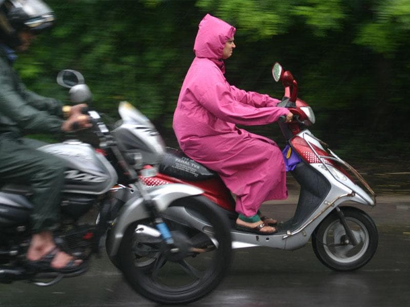 People ride two-wheelers in rains in Bhopal on Friday. (Bidesh Manna/HT photo)