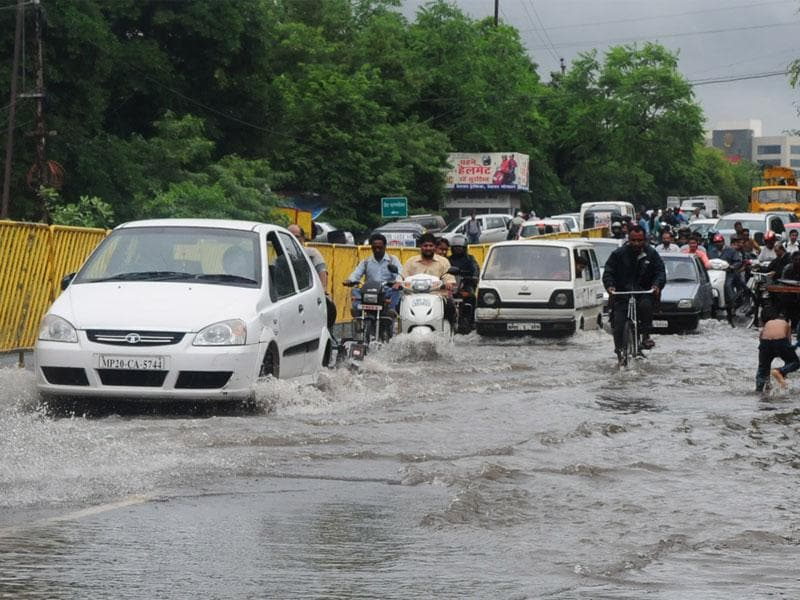 Vehicles move on waterlogged Hoshangabad Road near Reserve Bank after rains in Bhopal on Friday. (Mujeeb Faruqui/HT photo)
