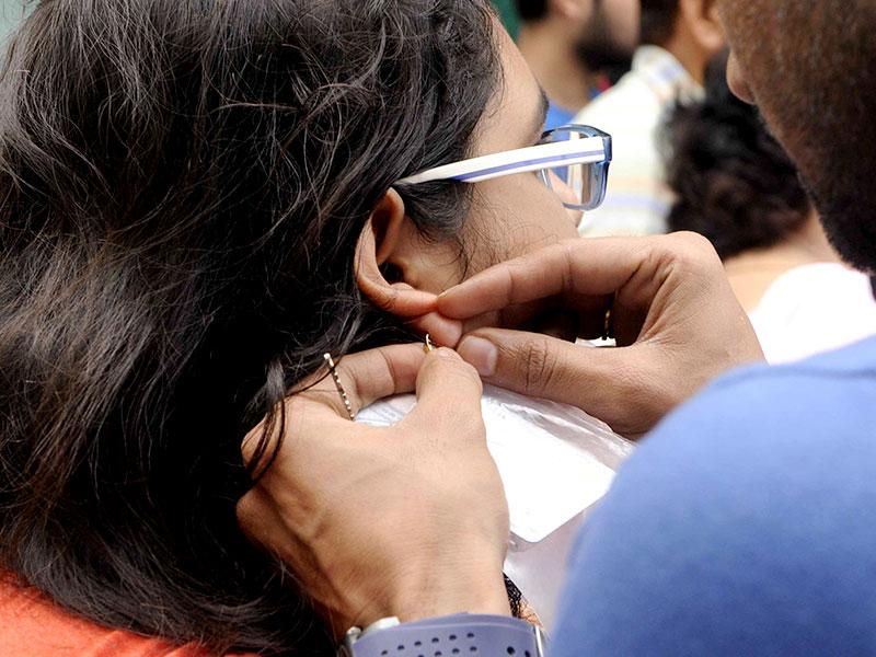 A boy removes gold rings from her AIPMT aspirant sister's ear as ear rings were not allowed due to dress code , at the entrance of Examination center at a school, in Jaipur, Rajasthan. (Himanshu Vyas/HT Photo)