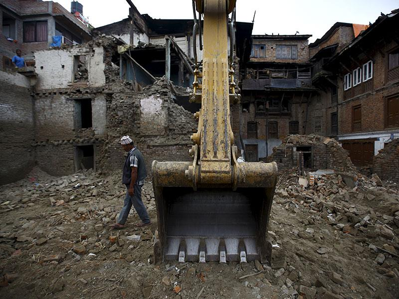 A man walks past an excavator parked near collapsed houses that were damaged during the earthquake in Bhaktapur. Two months after massive twin earthquakes killed 8,897 people in Nepal, nearly three million survivors -- many in mountainous, hard-to-reach areas -- still needed shelter, food and basic medical care as the yearly monsoon bore down on the Himalayan nation, the UN said in a report. (Reuters Photo)
